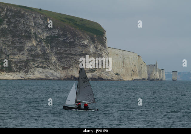 Swanage, UK -  12 May: A boat sails on the Swanage coast line with a view of the Old Harry Rocks in the background. - Stock Image