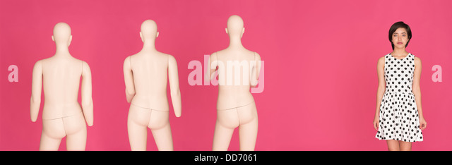 Conceptual portrait of young serious multiracial woman standing alone, left out from a group of mannequins - Stock Image