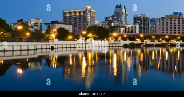 Downtown skyline of Orlando Florida reflects in Lake Lucerne at sunset - Stock Image