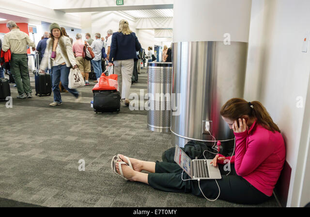Los Angeles California CA LAX international airport terminal concourse woman laptop computer charger electrical - Stock Image