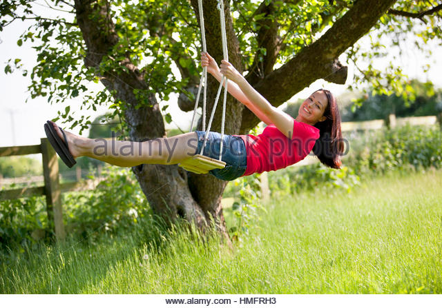 Portrait happy woman swinging on tree swing in sunny rural summer yard, carefree - Stock-Bilder
