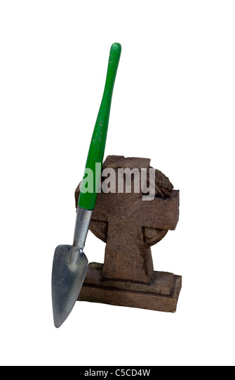 Cross shaped marble headstone with a shovel leaning against it - Path included - Stock Image