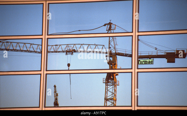 PICTURE CREDIT DOUG BLANE Tarmac crane on building site reflected in the glass building at Central Milton Keynes - Stock Image