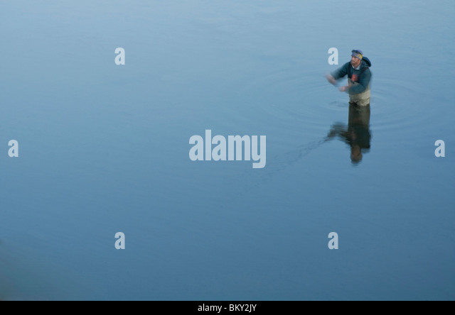 A young man fly fishes in flat, freezing cold water, on the Truckee River, California. - Stock Image