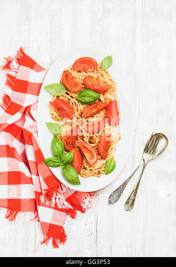 Spaghetti with roasted tomatoes and basil over white wooden background - Stock Image