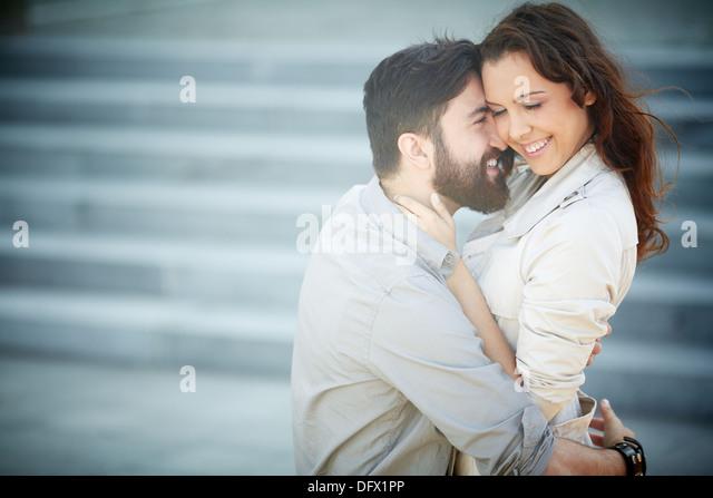 Image of joyful dates embracing outside - Stock Image