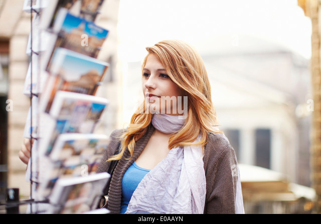 Young woman looking at postcards, Rome, Italy - Stock Image