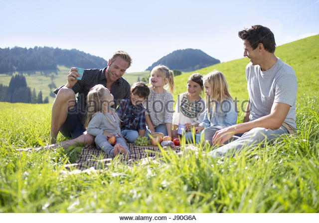 Fathers With Children Enjoying Countryside Picnic Together - Stock-Bilder