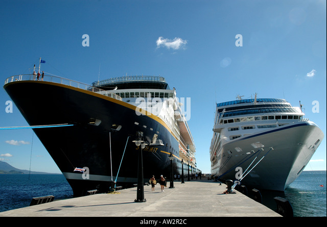 Cruise ships tied to pier size comparison megaship small ship - Stock Image