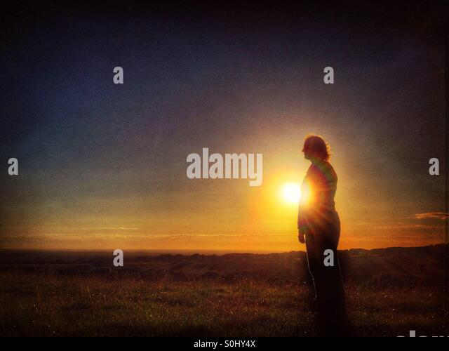 Woman alone in landscape at sunset - Stock Image