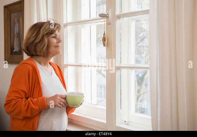 Side profile of a senior woman having cup of tea looking through window at home, Munich, Bavaria, Germany - Stock-Bilder