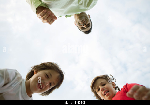 Father and sons outdoors, low angle view - Stock Image