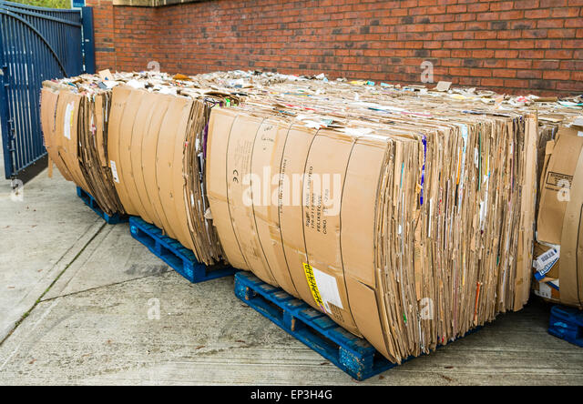 Stacks of used cardboard cartons on pallets ready for recycling in UK - Stock Image