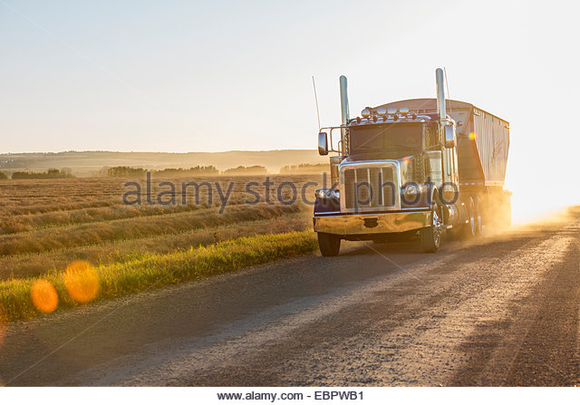 Semi-truck driving on sunny rural road - Stock Image