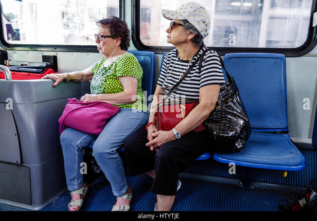 Miami Beach Florida South Beach Local public transportation bus shuttle circulator Hispanic woman senior sitting - Stock Image