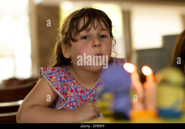 Portrait of girl (4-5) blowing out candles in blurred background - Stock Image
