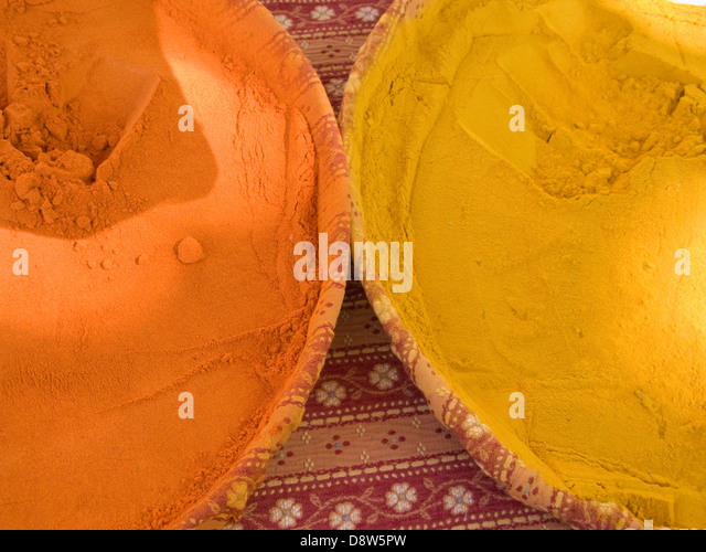 Part of two round dishes containing powered spices on a market stall, Arles, France - Stock Image