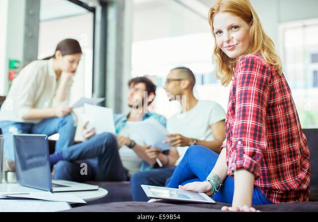 People using digital tablet in office - Stock Image