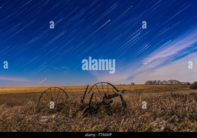 Orion, at right, rising in star trails behind the old plough, at home, on a bright moonlit night in November, with - Stock Image