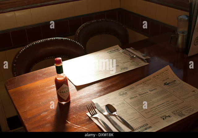Diner condiments sit on the table in a small town diner.  Place mats advertise local businesses. - Stock-Bilder