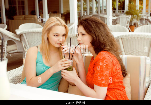 portrait of two pretty modern girl friends in cafe open air interior drinking and talking, having chat and coctail, - Stock Image