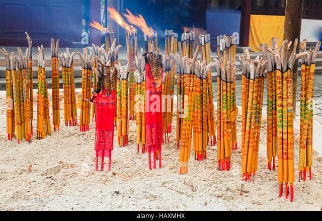 Burning bunches of orient sticks standing in sand turning into flame and ash in chinese ancient temple. - Stock Image