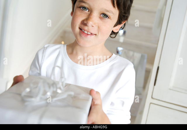 Portrait of a little boy offering a Christmas present, indoors - Stock Image