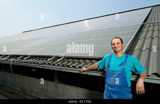 Portrait of farmer with solar panels on barn roof, Waldfeucht-Bocket, Germany - Stock Image
