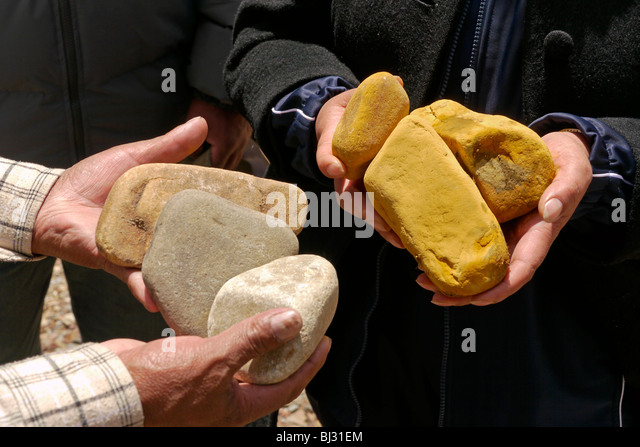 PERU Stones from river showing pollution (yellow) - Stock Image