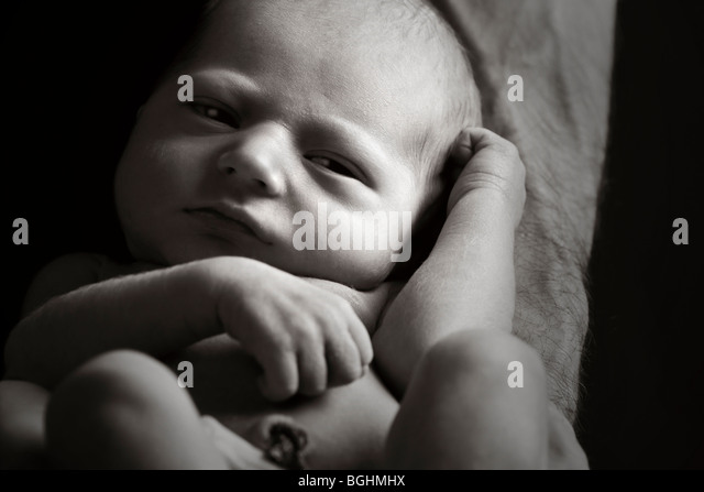 Beautiful Low Key Shot of a Newborn Baby on his Father's Arm - Stock Image