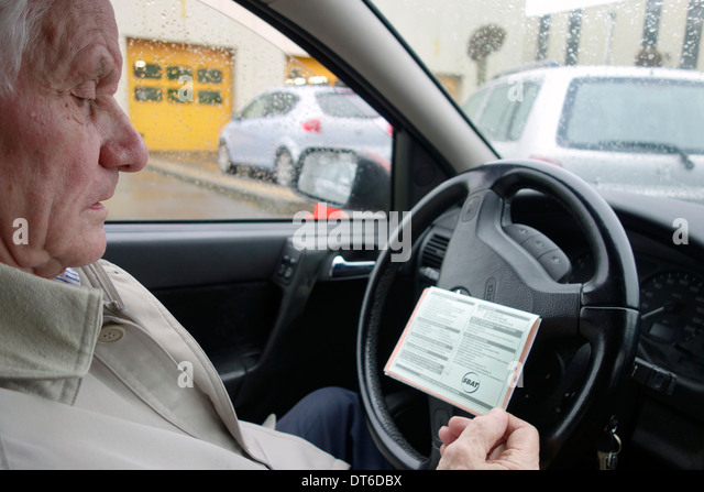 Elderly man looking at SBAT card in car while queuing in front of MOT testing centre for a yearly motor vehicle - Stock Image