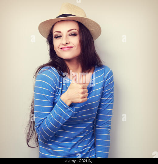 Very glad young woman in straw hat showing thumb up sign. Vintage toned portrait - Stock Image