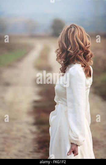 Woman with vintage bride dress looking at country road . Purity and innocence - Stock-Bilder