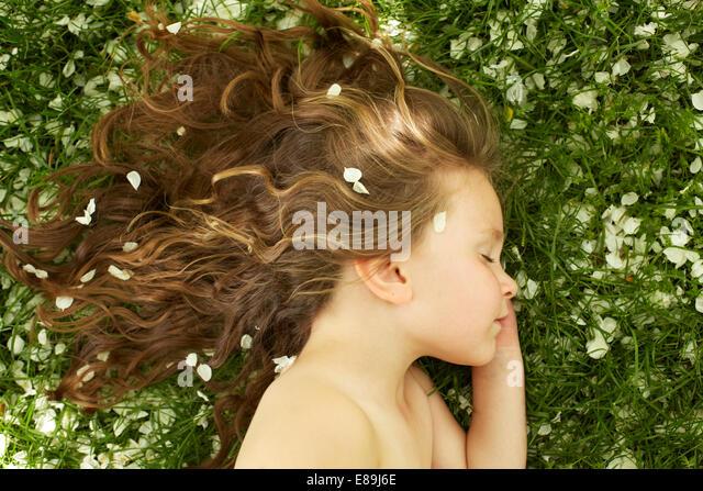 Girl sleeping in field with flower petals - Stock-Bilder