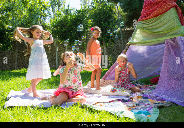 Girls blowing bubbles in summer garden party - Stock Image