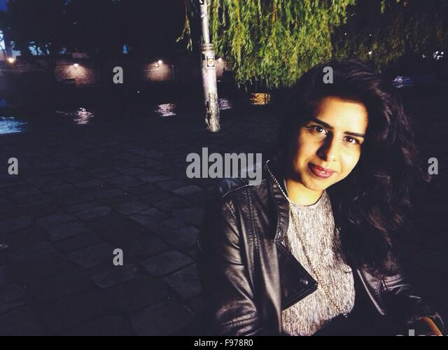Portrait Of Mid Adult Woman Outside Cafe At Night - Stock Image