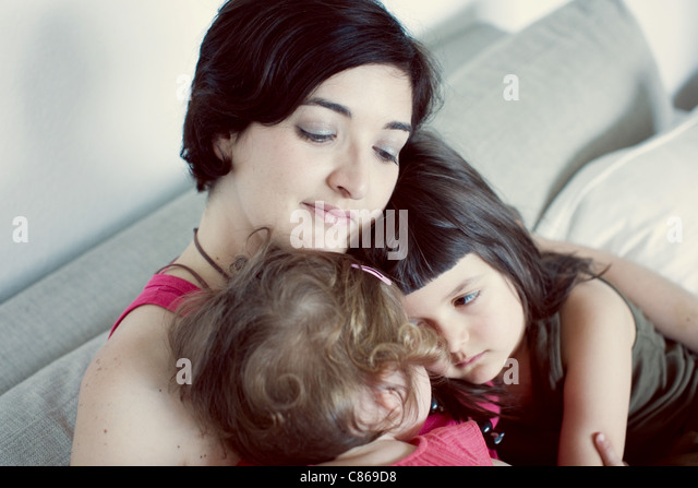 Mother and daughters embracing - Stock Image