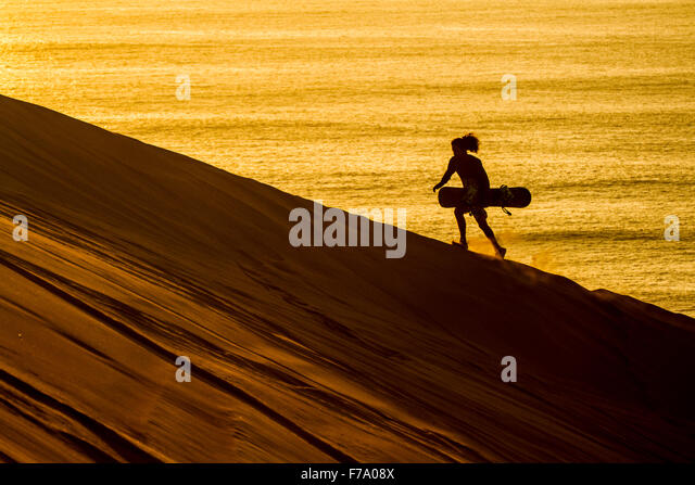 Silhouette of a sandboarder walking at sunset in Cerro Dragon, a sand dune located next to the city of Iquique, - Stock-Bilder