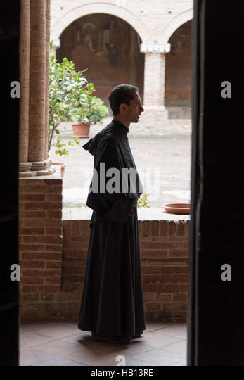 A catholic priest in the cloisters of St Nicholas's church - Stock Image