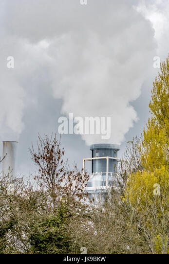 Steam venting into darkened skies from a chimney at a china clay plant at Par beach, Cornwall. - Stock Image