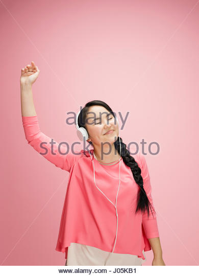Playful young Asian woman dancing and listening to music with headphones against pink background - Stock Image