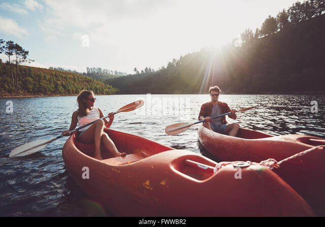Young couple kayaking on a lake together on a summer day. Man and woman canoeing on a sunny day. Enjoying a day - Stock Image