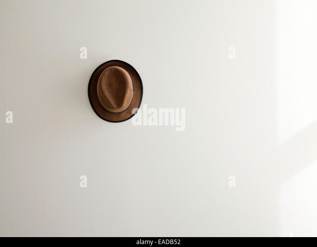 lone brown corduroy hat on white wall. - Stock Image