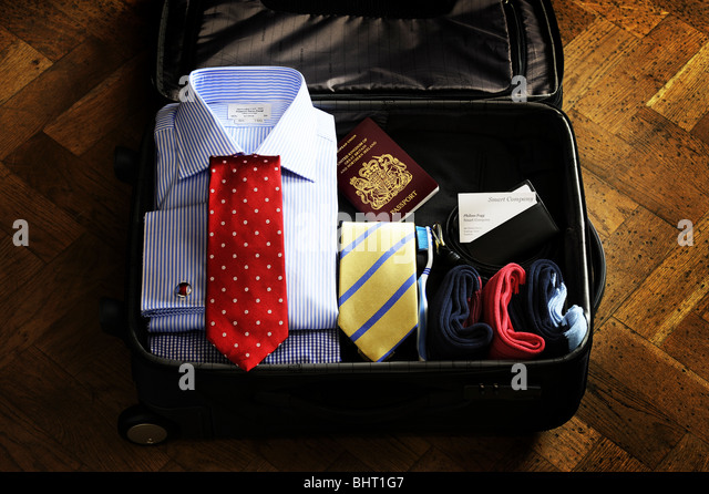 A suitcase containing travel items for a man - Stock-Bilder