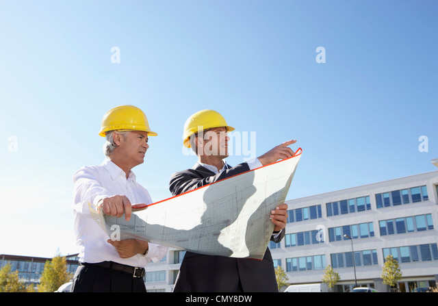 Germany, Bavaria, Munich, Engineers with blue print - Stock Image