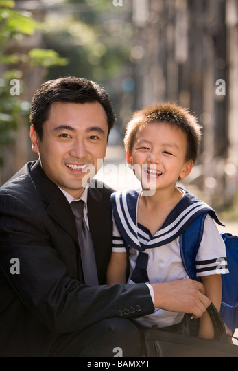 A father picks his son up from school - Stock Image