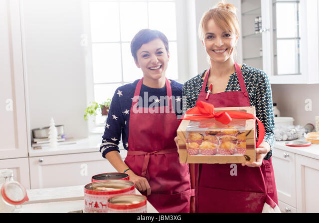 Portrait smiling female caterers showing wrapped box of pastries in kitchen - Stock-Bilder