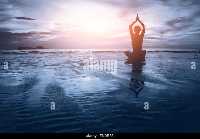 well being concept, beautiful sunset on the beach, woman practicing yoga - Stock-Bilder