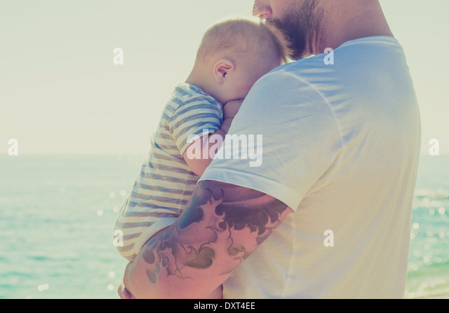 Close up of father holding baby son at beach - Stock Image