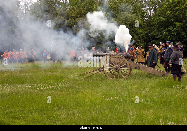 The canon fuse having just been lit the crew stand back waiting for the explosion. - Stock Image